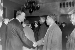 (Mayor or Governor) Theodore McKeldin shaking hands with Martin Jenkins, President of Morgan State College. Unidentified people and police officers in background. circa 1951. Paul Henderson, HEN.00.B1-067.